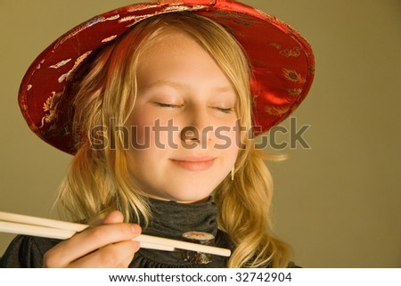 a thirteen years old girl at a sushi-bar with a sushi platter and chopsticks - stock photo