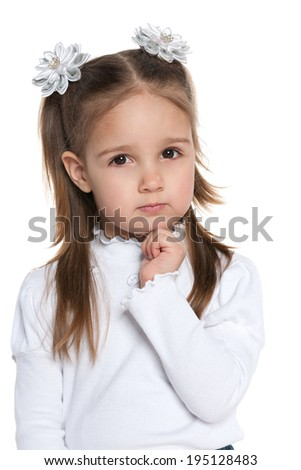 A thoughtful clever preschool girl on the white background - stock photo
