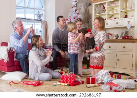A Three Generation Family at Christmas. Mum holds a small brown dog with a ribbon around its neck and everyone looks surprised.  - stock photo