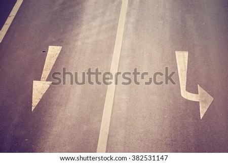 A three way arrow symbol on  road - stock photo