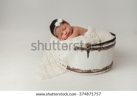 A three week old newborn baby girl sleeping in a little, wooden bucket. She is wearing a cream colored bow headband. Shot in the studio on a white background. - stock photo