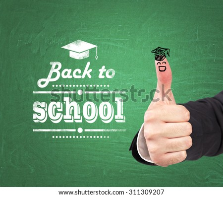 A thumb up with the sketch of the graduation hat and the words: ' back to school ' which are written on the green chalkboard. - stock photo
