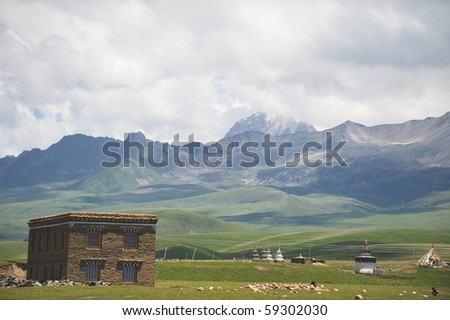 A tibetan house under the snow mountain. - stock photo