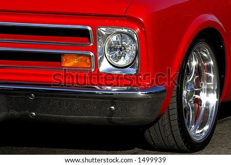 A tight shot of an old classic chevy showing only part of the front grill and side of the car. Nice graphic lines and bright colors. - stock photo