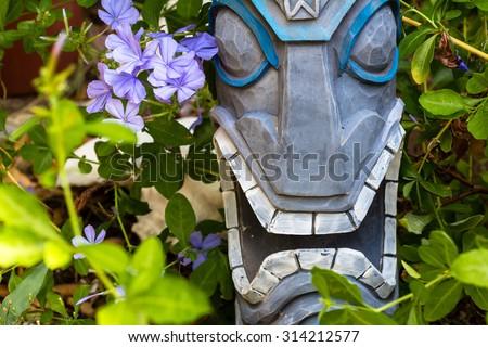 A Tiki statue en garden/ Tiki Garden flower/ A tiki head surrounded by Plumbago flowers. - stock photo