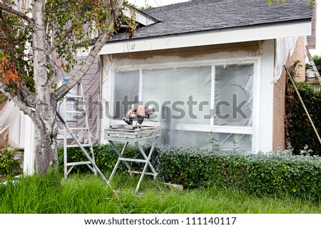 A tile saw and ladder in front of a plastic covered window during a home remodel. - stock photo