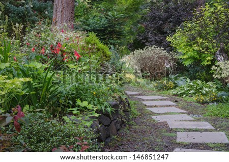 A tiled garden path curves through a wooded backyard garden. - stock photo