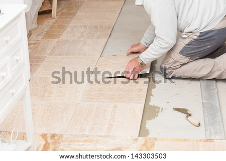 a tiler laying a tiled marble - stock photo