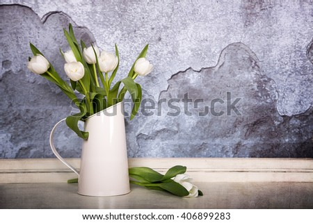 A tin jug filled with white tulips, over old plaster wall with grunge texture. Space for text - stock photo