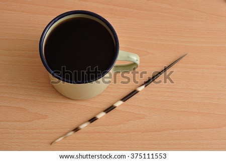 A tin mug filled with black coffee displayed with a porcupine spine - stock photo