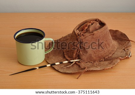 A tin mug filled with black coffee displayed with a porcupine spine and a leather hat  - stock photo