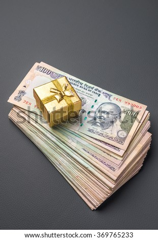 A tiny gift box placed on a hip of hundred rupee notes. Cash rewards concept. - stock photo