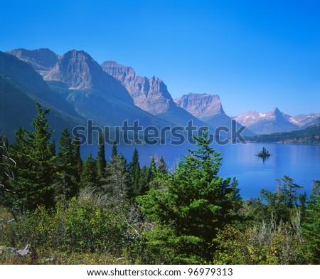 A Tiny Island On Saint Mary Lake In This Pastoral Mountain Lake Scene Typical Of Glacier National Park, Montana USA - stock photo