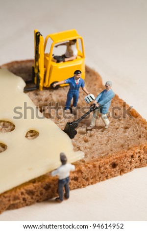 A tiny model figure of a foreman directs his miniature team in the making of a cheese sandwich using a forklift and loading equipment - stock photo