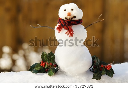 A tiny snowman with carrot nose, stick arms and red scarf, shallow depth of field, Christmas holly decorations, horizontal with copy space - stock photo