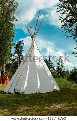 A tipi (also tepee and teepee) is a conical tent, traditionally made of animal skins, and wooden poles against blue sky - stock photo