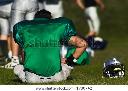 A tired football player is taking rest after the game. - stock photo