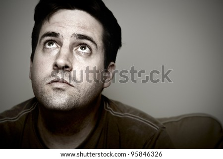 A tired man looks heavenward for guidance. - stock photo