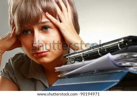 A tired young woman sitting at the desk, having a lot of paperwork to do, focus on a pile of documents - stock photo