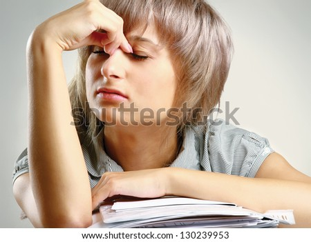 A tired young woman sitting at the desk, having a lot of paperwork to do, isolated on grey - stock photo