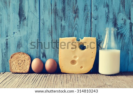 a toast, some eggs, a piece of Swiss cheese and a bottle with milk on a rustic wooden table, against a blue rustic wooden background, with a filter effect - stock photo