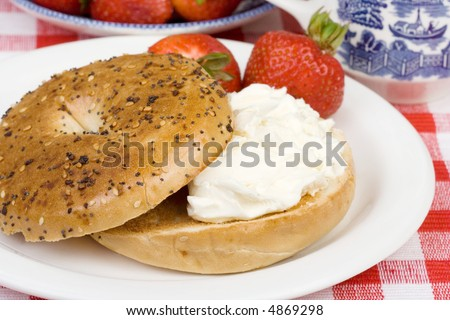 A toasted bagel with cream cheese for breakfast. Fresh strawberries on the side. Shallow dof. - stock photo