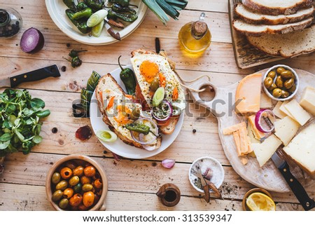A Toasted sandwich with smoked salmon and fried eggs and variety cheese cutting board with bowl olives and green leaves salad from above a wooden table. Country simple mediterranean food. - stock photo