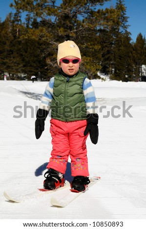 A toddler girl learns cross-country skiing at Lake Tahoe ski resort in Sierra Nevada mountains, California. - stock photo