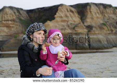 A toddler girl with her mother enjoys yogurt and energy bar on the beach just after sunset. Lit by natural available light only - no flash. - stock photo