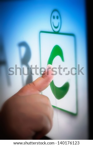 A toddlers' finger on a touchscreen tablet learning the alphabet using educational software. - stock photo