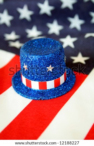 A top hat of blue glitter along with stars and stripes.  American flag is used as the background. - stock photo