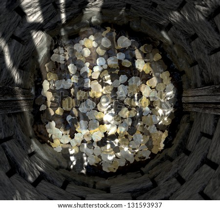 A top view looking into a brick wishing well with gold silver and bronze coins at the bottom covered in water - stock photo