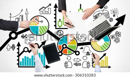 A top view of a brainstorm process. Business colleagues are analysing a business process. Laptop, tablet and legal pad on the table with drawn colourful charts which are drawn over the table. - stock photo