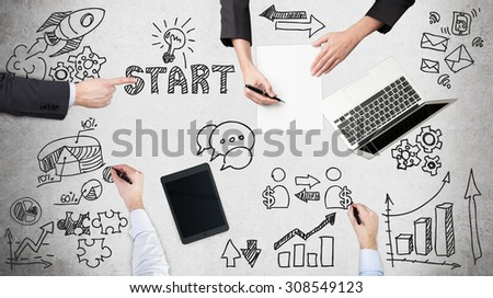 A top view of a brainstorm process. Business colleagues are build start up project. Laptop, tablet and legal pads on the table with drawn flowchart. - stock photo