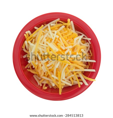 A top view of a red bowl of finely shredded white, cheddar, and mild cheddar cheese. - stock photo