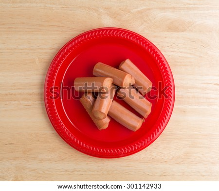 A top view of a red plate of canned smoked sausages on a cutting board. - stock photo