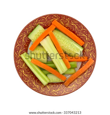 A top view of carrots, cucumbers and celery on a decorative gold filigree  maroon plate with a white background. - stock photo