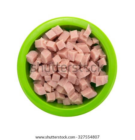 A top view of cooked and diced chunks of ham in a green bowl. - stock photo