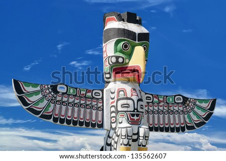 A totem wood pole in the blue cloudy background - stock photo