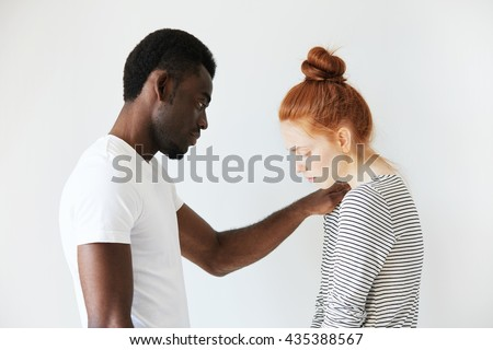 A touching scene of African American man comforting young redhead girl. He put his arm on her shoulder to sympathize her failure and to support her in hard times. Caucasian girl looks down in sorrow. - stock photo