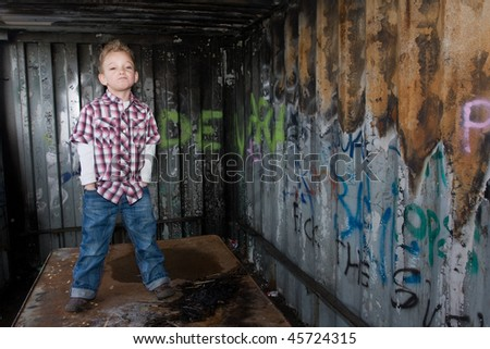 A tough guy at the graffiti wall. - stock photo