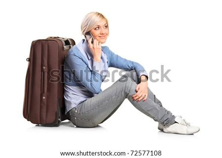 A tourist girl seated next to a suitcase talking on mobile phone isolated on white background - stock photo
