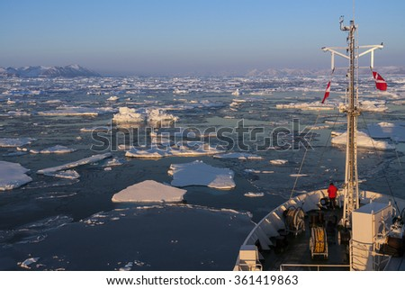 A tourist icebreaker and sea ice of the coast of eastern Greenland. - stock photo