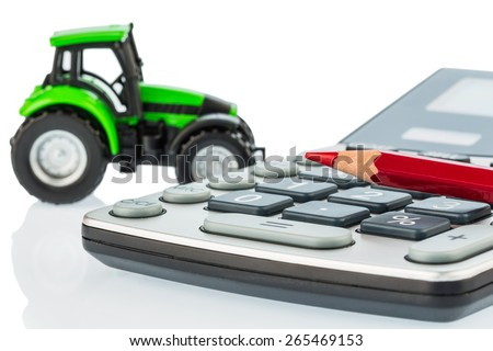 a tractor and a red pen lying on a calculator. cost of gasoline, wear and insurance. costs and subsidies in agriculture - stock photo