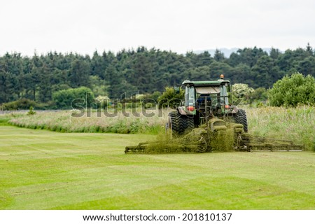A tractor being used to cut grass at a commercial turf growing farm in Scotland. - stock photo