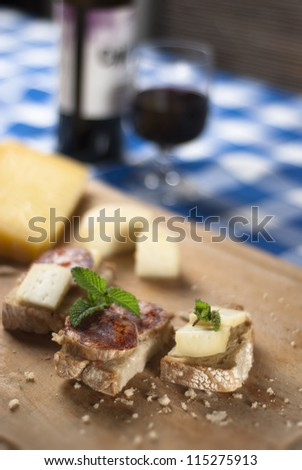 A traditional blue table with a plate with cheese and salami tapas and wine from Portugal - stock photo