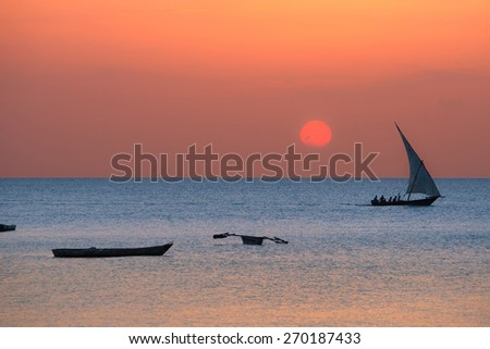 A traditional boat dhow off the coast of Zanzibar - stock photo