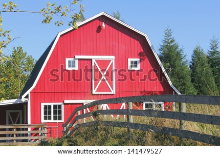 A traditional bright red barn with a white picket fence/Traditional Red Barn/A traditional North American red barn with a white picket fence. - stock photo