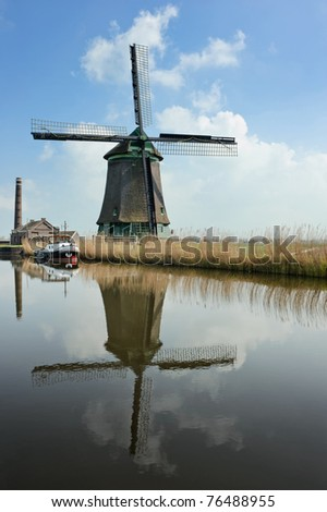 A traditional dutch windmill near the canal. Netherlands - stock photo