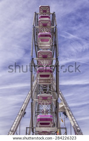 A traditional ferris wheel at a local carnival funfair. - stock photo